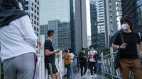 Warga berkumpul diatas JPO tanpa atap di Jakarta, Minggu (12/9/2021). Kasus baru positif Covid-19 di Indonesia per Minggu (12/9) bertambah sebanyak 3.779 kasus Jumlah tersebut membuat total kasus virus corona sejak awal pandemi mencapai 4.167.511 kasus. (Liputan6.com/Faizal Fanani)