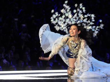 Model Tiongkok, Ming Xi jatuh tersungkur di atas catwalk Victoria's Secret Fashion Show 2017 saat memperagakan koleksi lingerie di Shanghai, Senin (20/11). Ming mengenakan busana warna biru dan silver dengan headpiece bunga yang rumit. (FRED DUFOUR/AFP)