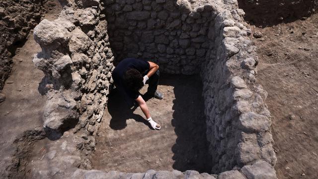 Arkeolog menunjukkan telur ayam berusia 1.000 tahun yang ditemukan selama penggalian di Kota Yavne, Israel, Rabu (9/6/2021). Otoritas Barang Antik Israel mengumumkan penemuan langka tersebut pada 9 Juni 2021. (Emmanuel DUNAND/AFP)