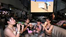 Pengunjung menikmati menonton film sambil berendam di Bathtub Cinema di atap gedung kawasan Shibuya, Tokyo, 17 Agustus 2018. Bathtub Cinema merupakan solusi kreatif yang ditawarkan oleh Afro&Co. untuk menikmati Tokyo di musim panas. (AFP/Kazuhiro NOGI)