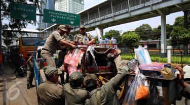 Petugas Satpol PP menertibkan lapak pedagang kaki lima (PKL) di pinggir jalan Kawasan Palmerah, Jakarta, Senin (17/10). Aktifitas ini dilakukan guna membuat jera  pedagang  yang nakal dan tetap nekat berjualan di Bahu jalan. (Liputan6.com/Johan Tallo)