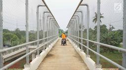 Pengendara sepeda motor melintasi JPO yang melintang di atas Tol Cijago Seksi II di Depok, Jawa Barat, Rabu (15/5). Meskipun berbahaya, namun curamnya akses JPO tidak menjadi penghalang bagi sebagian pemotor untuk menyeberang agar dapat memersingkat waktu tempuh. (Liputan6.com/immanuel Antonius)