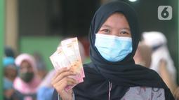 Warga penerima menunjukkan uang Bantuan Sosial Tunai (BST) bulan Januari di halaman Masjid Jami Al-Hidayah RW 01 Bedahan, Depok, Selasa (16/2/2021). Sekitar 159.470 Keluarga Penerima Manfaat (KPM) di Kota Depok menerima BST yang disalurkan PT Pos Indonesia pada Februari ini (merdeka.com/Arie Basuki)