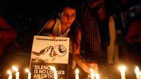 Seorang wanita India menyalakan lilin saat menggelar aksi protes kasus perkosaan di Ahmadabad, India (16/4). Selain itu dipicu juga oleh kasus penculikan serta pemerkosaan seorang gadis remaja di negara bagian utara Uttar Pradesh.(AP Photo / Ajit Solanki)