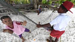 Anak-anak suku Byak Betew bermain di tepi pantai di pulau Saukabu, satu dari 1.500 pulau di Raja Ampat 20 Agustus 2017. Raja Ampat merupakan rumah bagi sekitar 1.400 jenis ikan dan 600 spesies karang. (AFP Photo/Goh Chai Hin)