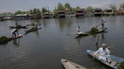 Para tukang perahu yang dipekerjakan oleh Pemerintah Jammu dan Kashmir menyingkirkan gulma dari Danau Dal di Srinagar, Kashmir, India, Rabu (22/7/2020). Danau Dal terkenal dengan airnya yang jernih dan tenang. (AP Photo/Dar Yasin)