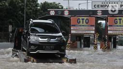 Sebuah mobil mogok diderek akibat nekat menerobos banjir di Tol Cempaka Putih, Jakarta, Minggu (23/2/2020). Banjir yang melanda kawasan tersebut menyebabkan Gerbang Tol Cempaka Putih tidak dioperasikan akibat terendam hingga ketinggian mencapai sepinggang orang dewasa. (merdeka.com/Iqbal S. Nugroho)