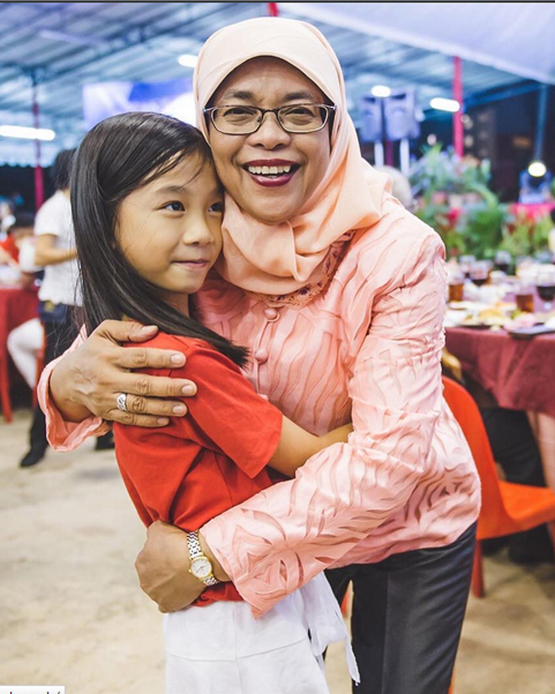 Riko (9 tahun) mendatangai Halimah Yacob untuk meminta tanda tangan dan mengucapkan terima kasih sambil memeluk, Singapura (14/8). (instagram.com/halimahyacob)