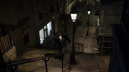 Seorang pria memakai masker berjalan di daerah Montmartre di Paris, Jumat (30/10/2020). Prancis memberlakukan kembali penguncian nasional selama sebulan yang bertujuan untuk memperlambat penyebaran virus, menutup semua bisnis yang tidak penting. (AP Photo/Lewis Joly)