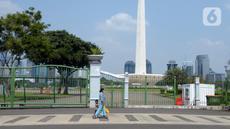 Warga berjalan di depan pagar Monumen Nasional (Monas), Jakarta, Sabtu (15/5/2021). Warga kecewa lantaran tempat wisata tersebut ditutup, padahal mereka datang untuk menikmati libur Idul Fitri 1442 Hijriah. (merdeka.com/Imam Buhori)