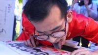 Han Xiaoming berhasil tuai pujian karena berhasil melukis dengan menggunakan lidahnya.