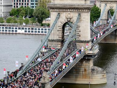 """Peserta aksi 'Maret for Life Hungaria' memenuhi jembatan Hungaria 'Lanchid' (Chain Bridge), Budapest, Minggu (16/4). The """"Maret for Life"""" memperingati ulang tahun dari Holocaust yang menyebabkan kematian ribuan korban. (AFP PHOTO / ATTILA KISBENEDEK)"""