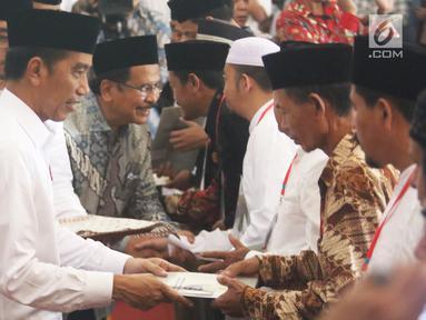 Presiden Joko Widodo saat membagikan sertifikat tanah wakaf di Masjid Raya Bani Umar, Tangerang Selatan, Jumat (22/2). Jokowi membagikan 351 sertifikat tanah wakaf untuk musala, tempat pendidikan dan pesantren. (Liputan6.com/Angga Yuniar)