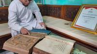 Kemas Andi Syarifuddin (49) menjadi generasi penerus yang menjaga Alquran tinta emas peninggalan Kesultanan Palembang Darussalam (Liputan6.com / Nefri Inge)