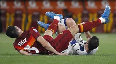 Bek AS Roma, Roger Ibanez saat melanggar gelandang Atalanta, Remo Freuler pada pertandingan lanjutan Liga Serie A Italia di Stadion Olimpiade Roma, Italia, Jumat (23/4/2021). AS Roma bermain atas Atalanta 1-1. (AP Photo/Alessandra Tarantino)