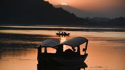 Nelayan menunggu di perahu kecil setelah memancing di Danau Dal saat matahari terbenam di Srinagar (9/9/2019). Danau terbesar kedua di propinsi Jammu dan Kashmir ini  merupakan pusat pariwisata dan rekreasi. (AFP Photo/Tauseef Mustafa)