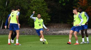 Gelandang Chelsea, Eden Hazard (tengah) menggiring bola saat mengikuti sesi latihan tim di Chelsea Training Ground, di Cobham, Surrey (22/5/2019). Chelsea akan bertanding melawan Arsenal pada babak Final Liga Europa pada 29  Mei di Baki Olimpiya Stadionu. (AFP Photo/Ben Stansall)