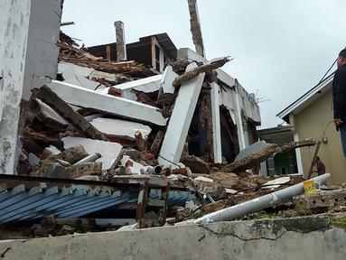 Penduduk desa memeriksa rumah mereka yang rusak setelah gempa magnitudo 5,1  di Sukabumi, Jawa Barat (10/3/2020). Menurut BMKG pusat gempa berada pada koordinat 6.81 LS dan 106.66 BT. (AFP/Handout/BNPB)
