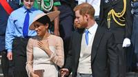 Duke dan Duchess of Sussex, Pangeran Harry dan Meghan Markle menghadiri pesta kebun Istana Buckingham di London, Selasa (22/5). Meghan juga memakai stocking warna kulit, mengikuti cara berbusana Putri Inggris lainnya. (Dominic Lipinski/Pool Photo via AP)