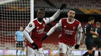 Gelandang Arsenal, Nicolas Pepe (kiri) melakukan selebrasi usai mencetak gol ke gawang Slavia Praha dalam laga leg pertama perempatfinal Liga Europa 2020/2021 di Emirates Stadium, London, Kamis (8/4/2021). Arsenal bermain imbang 1-1 dengan Slavia Praha. (AFP/Ian Kington)