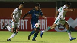 Striker Persib Bandung, Frets Butuan (tengah) berusaha melewati dua pemain Persebaya Surabaya dalam laga perempatfinal Piala Menpora 2021 di Stadion Maguwoharjo, Sleman, Minggu (11/4/2021). Persib menang 3-2 atas Persebaya. (Bola.com/M Iqbal Ichsan)