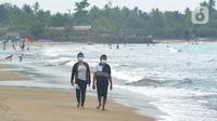 Wisatawan yang mengenakan masker menikmati suasana Pantai Anyer di Cilegon, Banten, Minggu (25/10/2020). Akhir pekan dimanfaatkan warga Jakarta dan sekitarnya untuk berwisata dengan tetap menerapkan protokol kesehatan Covid-19. (merdeka.com/Arie Basuki)