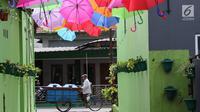 Pedagang melintas di Kampung Warna-Warni, Jalan Bhakti, Cimanggis, Depok, Jawa Barat, Rabu (21/3). Selain mempercantik lingkungan, warga ingin agar kampung ini bisa menjadi salah satu lokasi wisata alternatif di Depok. (Liputan6.com/Immanuel Antonius)