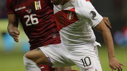 Gelandang timnas Peru, Christian Cueva berebut bola dengan gelandang Venezuela, Edson Castillo pada laga terakhir penyisihan Grup B  Copa America 2021 di Estadio Nacional Mane Garrincha, Minggu (27/6/2021). Menghadapi Venezuela, Peru menang tipis dengan skor 1-0. (AP Photo/Bruna Prado)