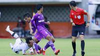 Gelandang Bali United, Hariono (kiri) terjatuh saat berebut bola dengan pemain Persita Tangerang dalam laga matchday ke-3 Grup D Piala Menpora 2021 di Stadion Maguwoharjo, Sleman, Jumat (2/4/2021). (Bola.com/M Iqbal Ichsan)