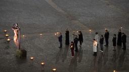 Sejumlah jemaat menghadiri upacara Via Crucis  atau Way of the Cross saat Jumat Agung di Lapangan St. Peter, Vatikan, Jumat  (10/4/2020). Pandemi virus corona COVID-19 membuat perayaan Jumat Agung berlangsung terbatas untuk menghindari penyebaran penyakit. (Claudio Peri/Pool Photo via AP)