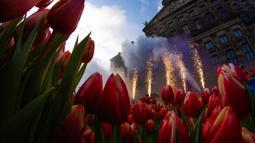 Kembang api dinyalakan ketika orang-orang menunggu untuk memetik tulip gratis pada Hari Bunga Tulip Nasional di Dam Square, Amsterdam, 18 Januari 2020. Hari Bunga Tulip Nasional ini menandai pembukaan musim bunga tulip untuk industri bunga Belanda.  (AP Photo/Peter Dejong)