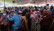 Warga menerima vaksin virus corona COVID-19 Sinovac di pusat vaksinasi massal darurat di lapangan sepak bola di Surabaya, Jawa Timur, Kamis (30/9/2021). Vaksinasi ini dalam rangka percepatan penanganan COVID-19 dan pemulihan ekonomi nasional. (Juni Kriswanto/AFP)