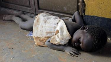 Seorang anak pengungsi dari Sudan Selatan tidur saat singgah di Pos Perbatasan Ngomoromo, Uganda, Senin (10/4). Sudan kini sedang mengalami bencana kelaparan, kekeringan dan perang saudara. (AFP PHOTO / ISAAC KASAMANI)