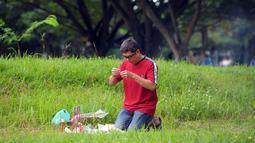 Seorang pria membakar dupa dan berdoa di sebuah kuburan massal korban tsunami Aceh di Aceh, Senin (26/12). Warga Aceh hari ini memperingati 12 tahun gempa dahsyat berkekuatan 9,3 SR disusul tsunami pada Minggu 26 Desember 2004. (CHAIDEER MAHYUDDIN/AFP)