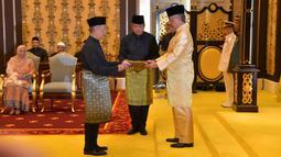 Muhyiddin Yassin (kiri) menerima dokumen dari Raja Sultan Abdullah Sultan Ahmad Shah (kanan) sebelum disumpah sebagai Perdana Menteri Malaysia di Istana Negara, Kuala Lumpur, Minggu (1/3/2020). Muhyiddin Yassin menggantikan Mahathir Mohamad. (MASZUANDI ADNAN/MALAYSIA'S DEPARTMENT OF INFORMATION/AFP)