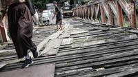 Anak anak melintasi jembatan dari kayu yang menjadi penghubung antara Jalan Karet Pasar Baru VII, Karet Tengsin dan Jalan Pam Baru, Bendungan Hilir, Tanah Abang, Rabu (30/1). (Liputan6.com/Faizal Fanani)