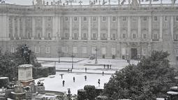 Orang-orang berjalan melewati salju di luar Istana Kerajaan, Madrid, Spanyol, Jumat (8/1/2021). Salju tebal menutupi hingga setengah dari Spanyol dan menyebabkan penurunan suhu yang besar. (GABRIEL BOUYS/AFP)