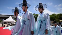 """Para pria muda mengenakan pakaian tradisional untuk menghadiri upacara """"Coming of Age"""" di Namsan Hanok Village, Seoul, Senin (20/5/2019). Di Korea Selatan, Coming of Age Day atau hari kedewasaan dirayakan secara nasional setiap tahun pada hari Senin ketiga di bulan Mei. (Ed JONES/AFP)"""