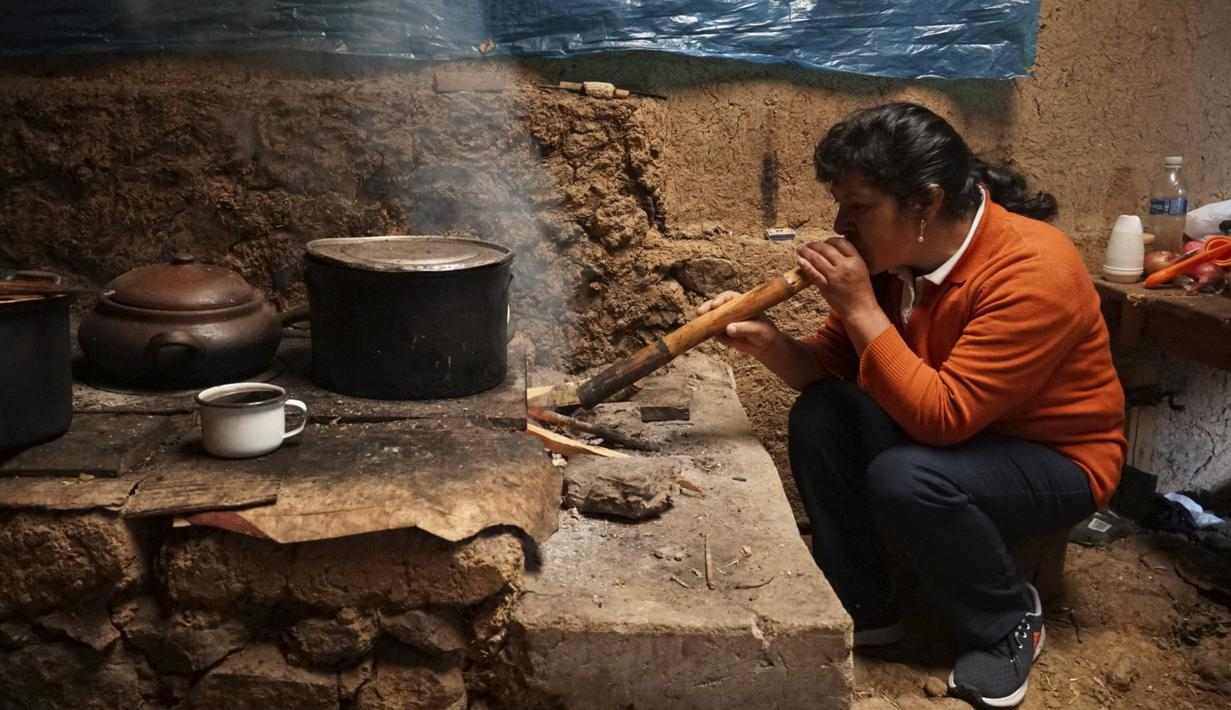 Calon ibu negara Peru, Lilia Paredes (48) meniupkan buluh bambu untuk menyalakan api di rumahnya yang terbuat dari batu bata di pedesaan Chugur, 22 Juli 2021. Suaminya, Pedro Castillo yang merupakan mantan guru dan pemimpin serikat pekerja memenangkan pemilihan presiden Peru. (AP/Franklin Briceno)