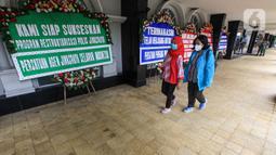 Dua orang wanita berjalan dekat karangan bunga di halaman Kantor PT Asuransi Jiwasraya (Persero), Jakarta, Selasa (15/12/2020). Karangan bunga tersebut berisi ucapan dukungan kepada manajemen baru Jiwasraya dalam penyelamatan polis melalui program restrukturisasi. (Liputan6.com/Faizal Fanani)
