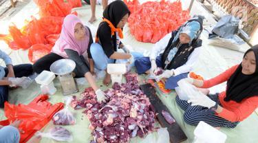 Panitia memotong daging kurban sebelum dibagikan ke warga sekitar Masjid  Al-Kahfi, Griya Pamulang 2, Tangerang Selatan, Banten, Rabu (22/8). Semarak Idul Adha 1439 H membuat warga gotong royong mendistribusikan daging kurban. (Merdeka.com/Dwi Narwoko)