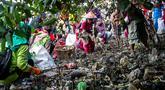 Anak-anak memungut sampah yang berserakan di sekitar kawasan pantai di Surabaya, Jawa Timur, Sabtu (21/9/2019).Aksi tersebut sebagai wujud kepedulian terhadap kebersihan lingkungan sekaligus dalam rangka memperingati World Cleanup Day 2019.  (JUNI KRISWANTO / AFP)