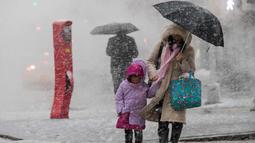 Pejalan kaki berjalan di sepanjang St. Delancey saat badai salju di New York (7/3). Badai salju kedua yang melanda New York dalam waktu seminggu ini diperkirakan akan membawa angin kencang. (AP Photo / Mary Altaffer)