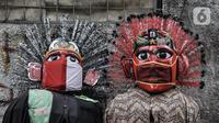 Ondel-ondel yang mengenakan masker dipajang di Kramat Pulo, Jakarta, Rabu (10/2/2021). Pendapatan sejumlah sanggar ondel-ondel di Kramat Pulo merosot karena larangan menggelar pesta pernikahan atau sejenisnya selama pandemi. (merdeka.com/Iqbal S. Nugroho)