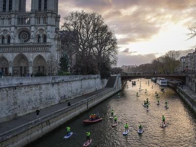 Para peserta mengambil bagian dalam Nautic Paddle Race dekat katedral Notre-Dame di Paris, Minggu (9/12). Sekitar 800 orang mengikuti lomba dayung sambil berdiri terbesar di dunia sejauh 11 km menyeberangi sungai Seine. (Lucas BARIOULET/AFP)