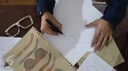 Pemilik brand kacamata kayu Kabau Bonny Andrew sedang mensketsa kacamata di studio Namines, Jakarta, Kamis (18/08). Kacamata kabau bisa di pesan dengan sesuai permintaan yang jadi selama 1 minggu. (Liputan6.com/Herman Zakharia)