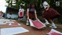 Sejumlah murid menjemur kertas daur ulang di SD Tarakanita 5, Jakarta, Sabtu (12/1). Selain memperingati HUT ke-45 SD tersebut, pembuatan seribu kertas daur ulang ini juga untuk mengurangi sampah di Jakarta yang belum teratasi. (Merdeka.com/Imam Buhori)
