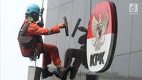 Pekerja membersihkan debu yang menempel pada tembok dan logo KPK di Gedung KPK, Jakarta, Rabu (21/11). Pemerintahan Provinsi Papua mendapat skor terendah yaitu 52,91. (Merdeka.com/Dwi Narwoko)