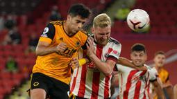 Penyerang Wolverhampton Wanderers, Raul Jimenez, berebut bola dengan pemain Sheffield United pada laga Liga Inggris di Bramall Lane, Selasa (15/9/2020). Wolverhampton menang 2-0 atas Sheffield United. (AFP/Dave Thompson/pool)
