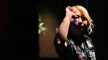 Mikuru Suzuki bersiap untuk melempar anak panah saat bermain darts di Tokyo, Jepang, 8 April 2019. Wanita berusia 37 tahun ini memiliki julukan 'The Miracle' karena keahliannya bermain darts. (CHARLY TRIBALLEAU/AFP)